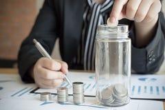 As jovens mulheres salvar o dinheiro fazendo a renda E use a calculadora futura do dinheiro fotografia de stock