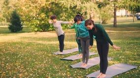 As jovens senhoras delgadas estão praticando a ioga fora no parque sob a orientação de professor experiente, a mulher está faland video estoque