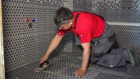 As junções de enchimento da telha do homem sujo do trabalhador com rebocam o enchimento filme