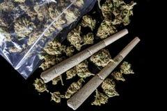 As junções e os botões médicos do cannabis dispersaram do preto do pacote acima foto de stock