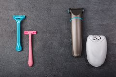 As lâminas, um depilator e um ajustador estão em um fundo cinzento fotografia de stock