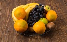 As laranjas, as maçãs, as bananas e as uvas estão no prato Fotografia de Stock