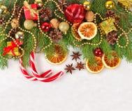 As laranjas e os cones secados, as decorações do Natal e o spruse ramificam fotografia de stock