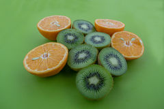 As laranjas e os quivis catted na metade na superfície do verde fotos de stock royalty free