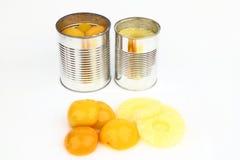 As latas com pêssegos e abacaxis Foto de Stock