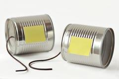 As latas de lata telefonam com nota quebrada da corda e do papel - uma comunicação imagens de stock