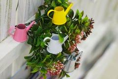 As latas molhando coloridas pequenas jardinam miniatura foto de stock