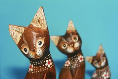 as lembranças marrons de madeira do gato sentam-se em um fundo azul imagem de stock royalty free