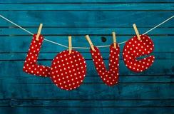 As letras da inscrição da tela amam às bolinhas vermelhos em pregadores de roupa em de madeira Imagem de Stock Royalty Free