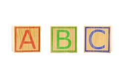 As letras de ABC em três cubos de madeira marrons alinharam Foto de Stock Royalty Free