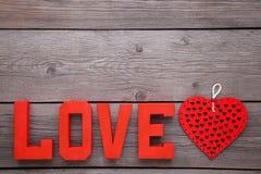 As letras vermelhas amam e coração no fundo cinzento Palavra do amor fotos de stock