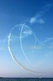 As linhas brancas das curvas afogam-se pela trilha dos aviões e do mar no fundo do céu azul, vista vertical Imagem de Stock Royalty Free