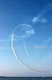 As linhas brancas das curvas afogam-se pela trilha dos aviões e do mar no fundo do céu azul, vista vertical Fotos de Stock Royalty Free