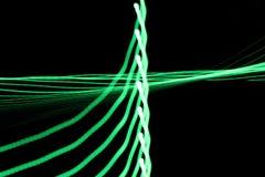 As linhas claras de néon e as curvas verdes abstraem a imagem no fundo preto Imagem de Stock