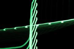 As linhas claras de néon e as curvas verdes abstraem a imagem no fundo preto Foto de Stock Royalty Free