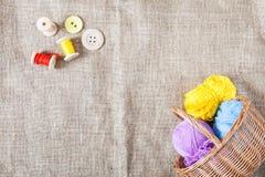 As linhas coloridas e os botões de madeira e uma cesta de vime estão no pano de saco no canto do quadro imagens de stock royalty free