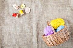 As linhas coloridas e os botões de madeira e uma cesta de vime estão no pano de saco no canto do quadro fotos de stock