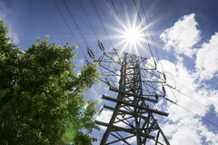 As linhas de alta tensão e Sun brilhante ilustram necessidades do poder do verão Imagens de Stock