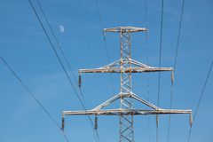 As linhas elétricas cancelam o céu azul e a lua no inverno foto de stock