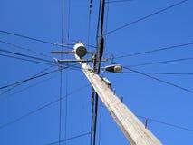 As linhas elétricas de alta tensão cruzam-se em um polo de serviço público de madeira com Imagens de Stock