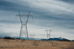 As linhas elétricas de alta tensão na montanha abandonam contra o céu azul Fotografia de Stock
