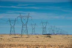 As linhas elétricas de alta tensão na montanha abandonam contra o céu azul Imagens de Stock
