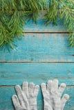 as luvas com abeto ramificam no fundo de madeira azul fotos de stock