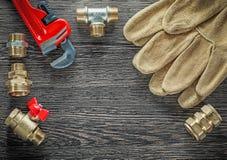 As luvas da segurança que sondam conectores da chave de tubulação molham a válvula cortejam sobre fotografia de stock