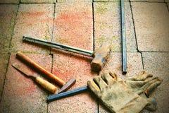 As luvas, o martelo, o formão, a vara de aço e as sapatas puseram sobre o tijolo Imagens de Stock