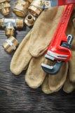 As luvas protetoras dos conectores da tubulação da chave de macaco do encanamento molham v fotos de stock royalty free
