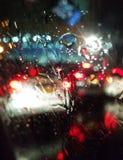 As luzes da cidade da noite através dos pingos de chuva obscuros foto de stock royalty free