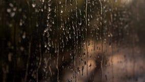 As luzes da cidade da noite Vidro de Misted Pingos de chuva l?quidos na janela Auto sinais Defocused no dia do por do sol Tristez video estoque