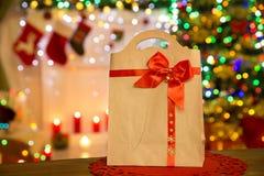 As luzes de Natal do saco de papel, Xmas decoraram o pacote do presente com vermelho Imagens de Stock