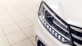 As luzes dianteiras do carro branco moderno com diodo emissor de luz O carro está na sala de exposições em um dia ensolarado foto de stock