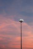 As luzes do estádio giraram sobre e um por do sol bonito no backgroun Imagem de Stock Royalty Free
