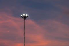 As luzes do estádio giraram sobre e um por do sol bonito no backgroun Fotos de Stock
