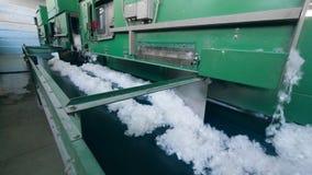As máquinas da fábrica funcionam com a fibra de poliéster branca, movendo o em um transporte video estoque