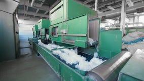 As máquinas da planta empurram a fibra sintética em um transporte longo video estoque