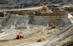 As máquinas escavadoras extraem a argila na pedreira industrial aberta Fotografia de Stock Royalty Free