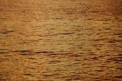As máscaras de ondinhas Amarelo-alaranjadas da água do oceano fora da costa norte do crepúsculo refletindo de Oahu iluminam-se Foto de Stock