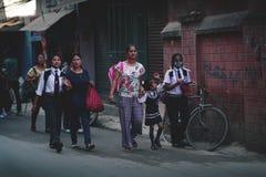 As mães tomam-lhe crianças à escola na rua de Thamel Imagens de Stock