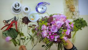 As mãos aéreas de um florista unem um ramalhete das flores video estoque