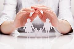 As mãos abraçam a família (o conceito) Foto de Stock