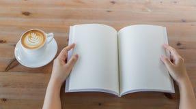 As mãos abrem o catálogo vazio, compartimentos, zombaria do livro acima na tabela de madeira Imagens de Stock