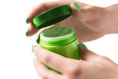 As mãos abrem um frasco do creme Fotos de Stock