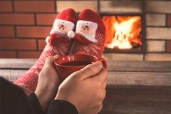 As mãos adolescentes do ` s guardam uma xícara de café vermelha na frente da chaminé Feriado do Natal imagem de stock royalty free