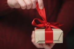 As mãos adolescentes fêmeas abrem a caixa de presente de papel do ofício com curva vermelha Foto de Stock