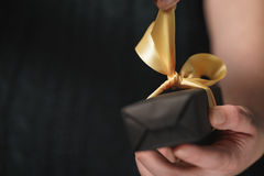 As mãos adolescentes fêmeas abrem a caixa de presente de papel preta com curva amarela Imagens de Stock Royalty Free