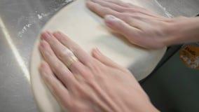 As mãos amassam a massa para a pizza no desktop filme