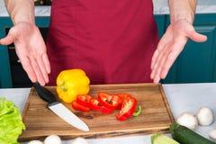 As mãos apontam no vegetal das fatias da pimenta e na faca cerâmica Imagens de Stock